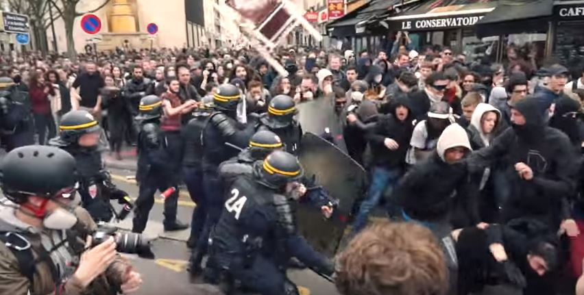 On the same day migrants war in Paris, violent socialists hurl chair at riot police. (YouTube screenshot)