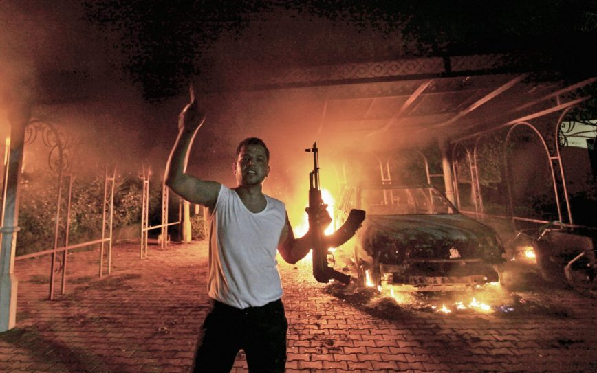A protester reacts as the U.S. Consulate in Benghazi is seen in flames